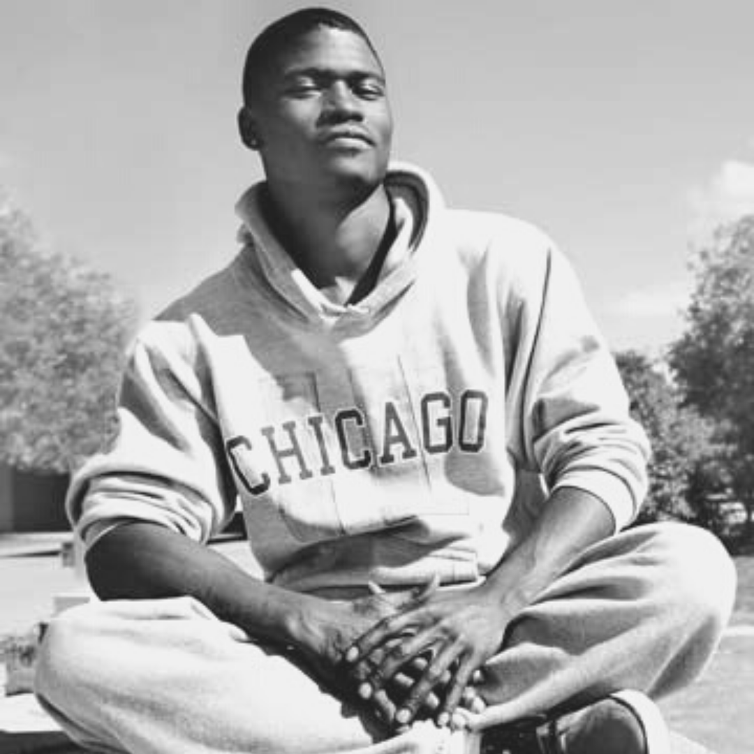 A young man in a Chicago sweatshirt sitting cross-legged
