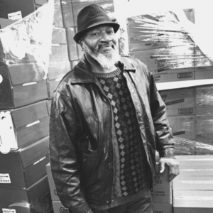 A man wearing a hat and leather coat in a warehouse