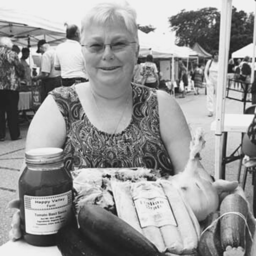 A woman with glasses at a farmers market showing her purchases