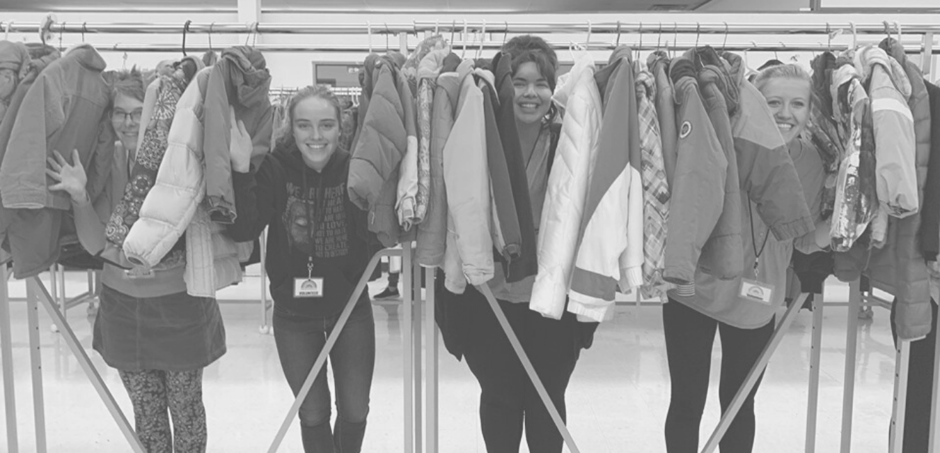 smiling volunteers in a rack of donated coats at Koats for Kids